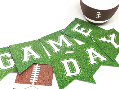 Green banner featuring white text reading game day and two football patterns on end perfect for a football party or tailgate