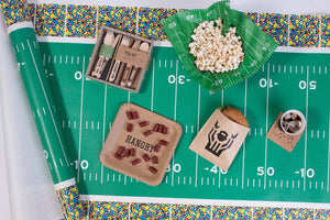 cardboard football coaster displayed with football table runner and other grub paper party supplies