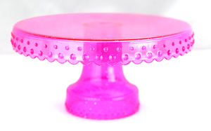 pink transparent plastic cake stand with glitter flecks.  Bright pink. Beaded edge