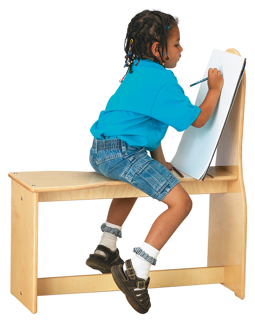 Child sitting on a wooden horse frame drawing on easel