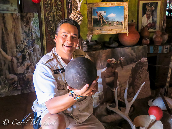 Man holding ball in front of picture of ancient ball game