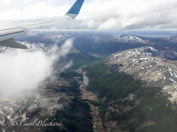 View from airplane window of rugged terrain, snow, river