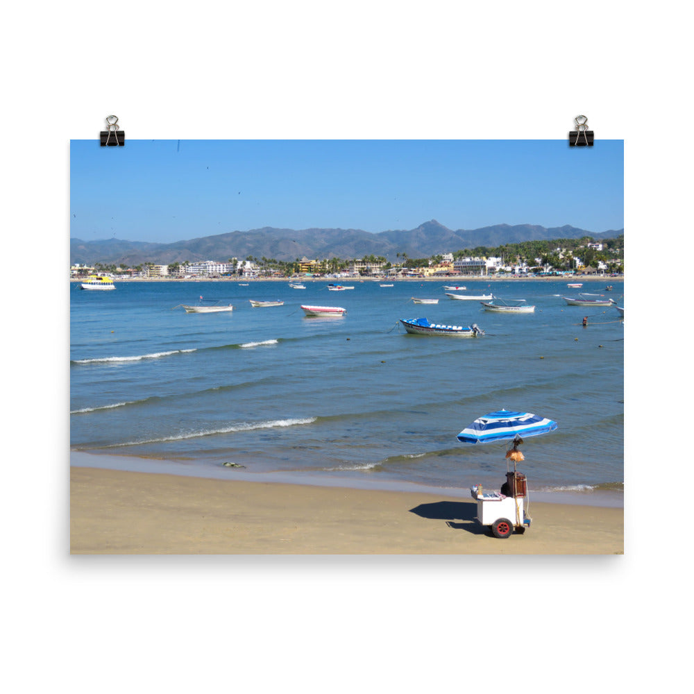 Beach with vibrant blues, boats, and mountains behind - Print