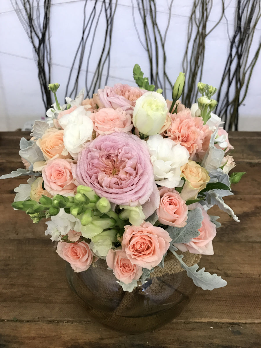 Pastel fresh flower arrangement in large fishbowl vase with roses and other seasonal fresh flowers