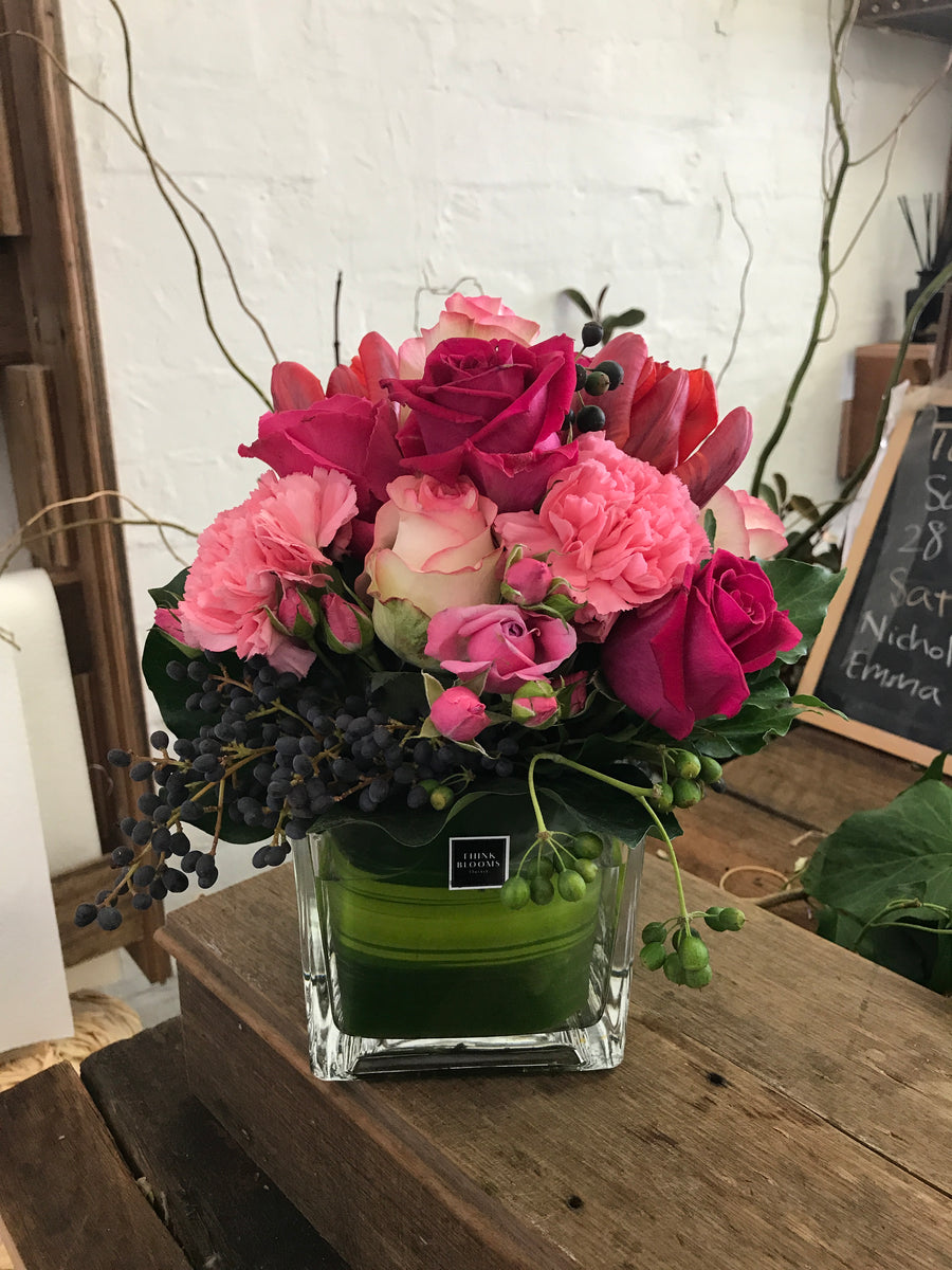 hot pink fresh posy in vase with bright pink color roses and other seasonal fresh flowers