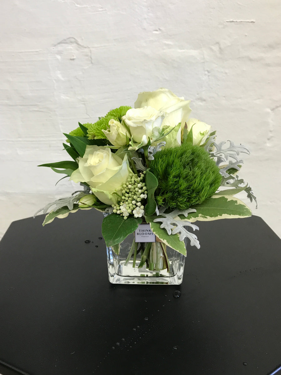 white and green fresh little posy in vase with white roses, white lisianthus and other seasonal fresh flowers