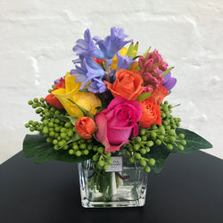 colorful fresh little posy in vase with bright color roses and other seasonal fresh flowers
