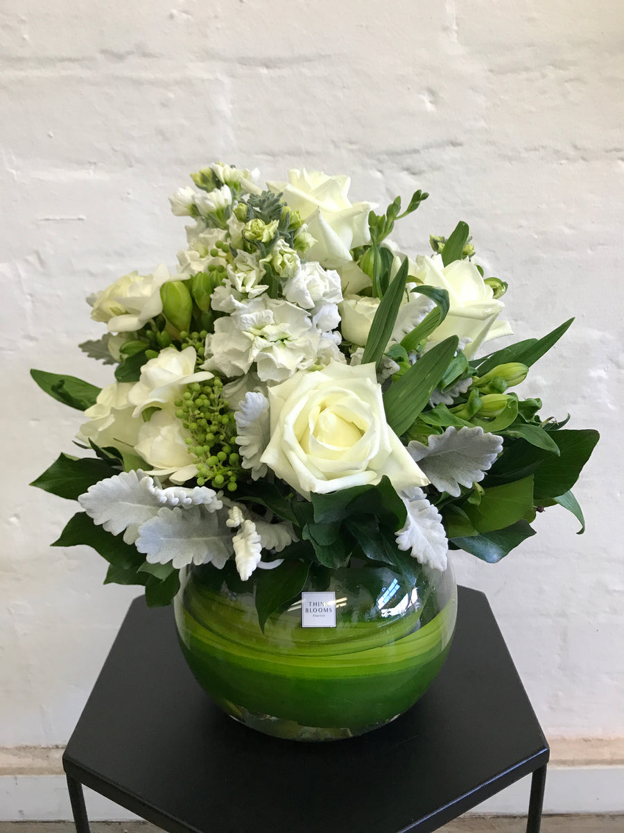 White and green fresh flower arrangement in medium fishbowl vase with white roses, white stock and other seasonal fresh flowers