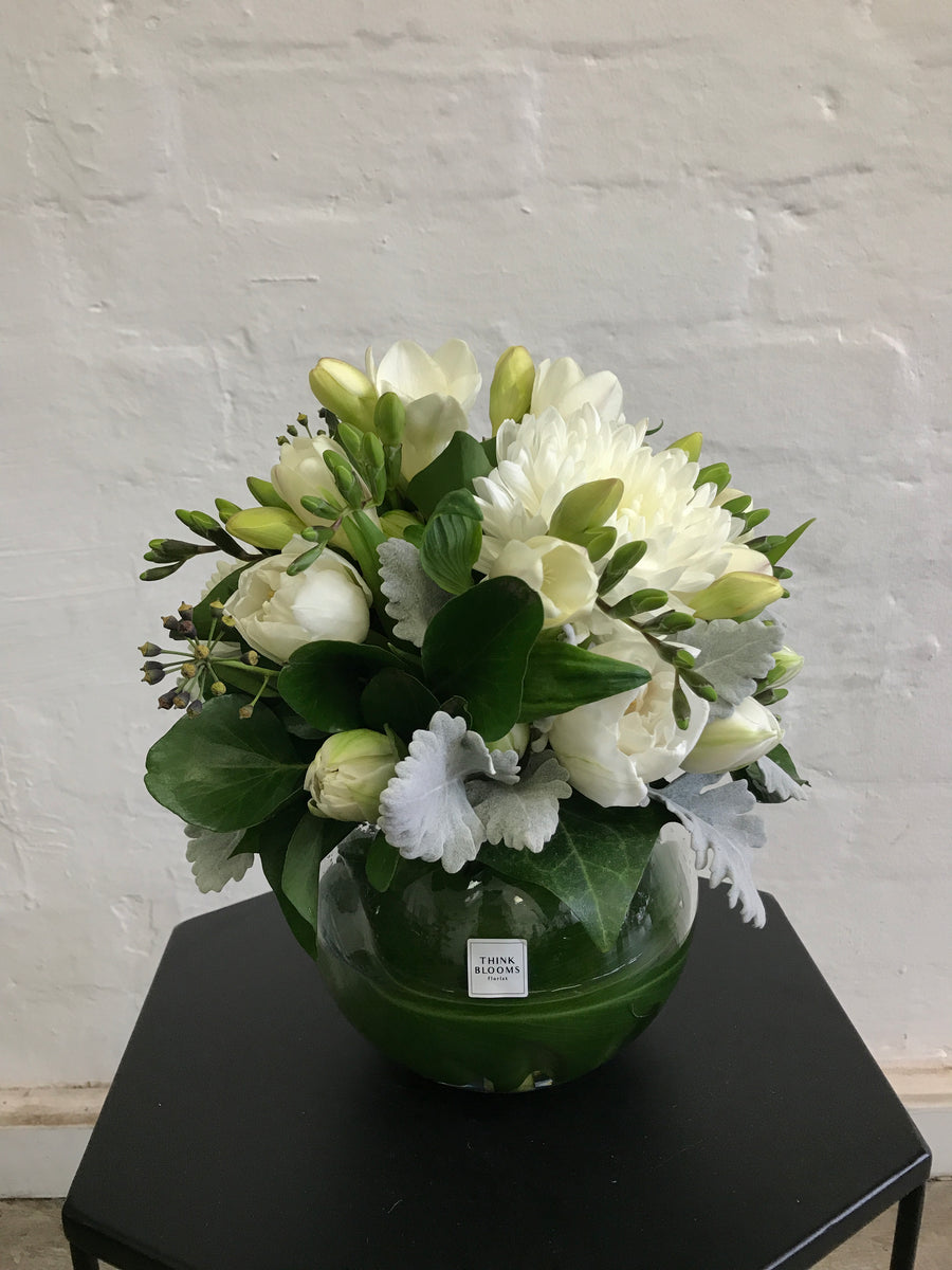 White and green fresh flower arrangement in medium fishbowl vase with white roses, white chrysanthmum, white freesia and other seasonal fresh flowers