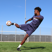 male athlete volleying the senda orange/navy blue valor match soccer ball