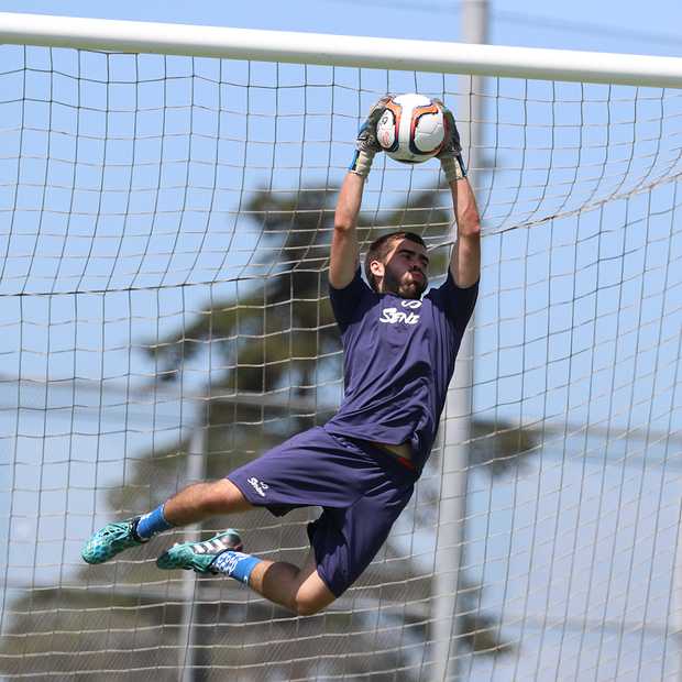 male goalkeeper catching the senda orange/navy blue valor match soccer ball