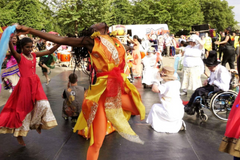 Carnival celebrations. Performers in vibrant colourful costume, dancing.