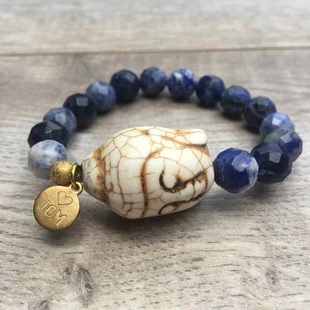 Blue gemstone beads with White Buddha accent.