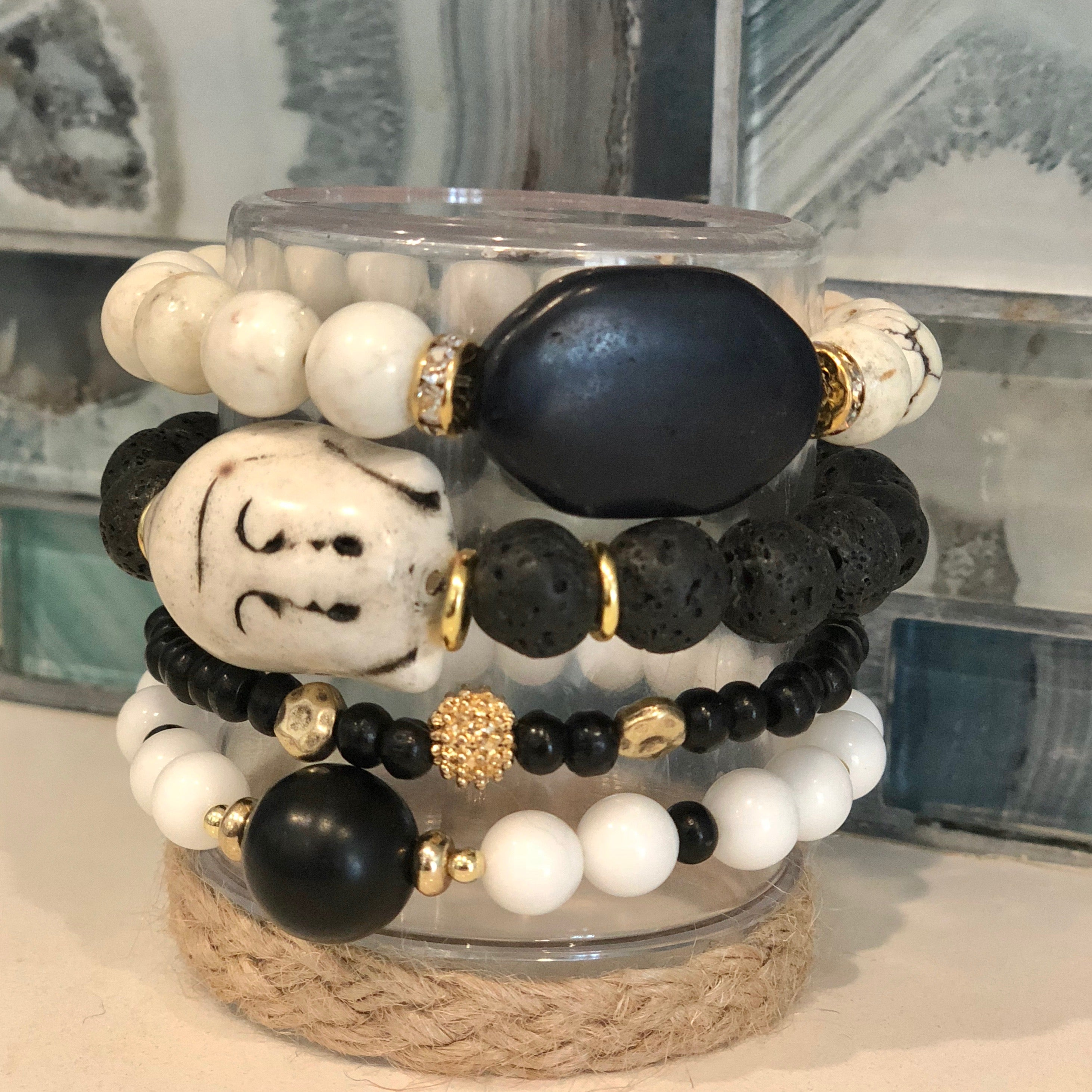Set of 4 gemstone beaded bracelets with a Howlite Buddha centerpiece. Lava stone beads mixed with white onyx and wood beads with gold accents.