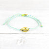Gradient, colourful surf anklet centred with a golden shell charm