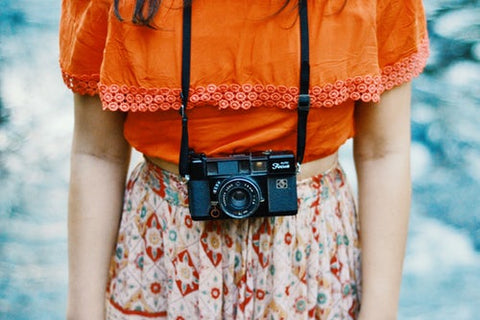 girl standing in an orange shirt and flowered skirt holding a camera