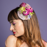 purple floral fascinator hat with lilac base and greenery