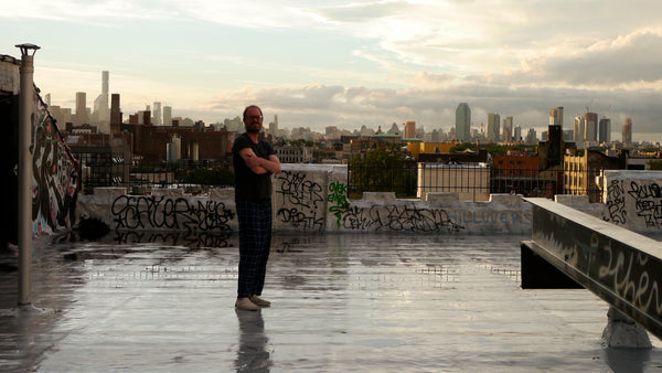 My husband on the roof with the NYC skyline in the background