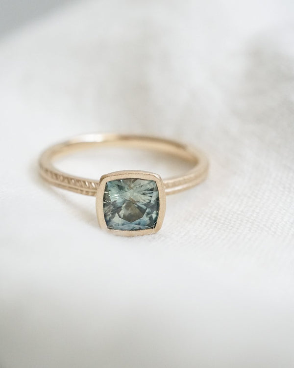 Cushion cut green montana sapphire on Wisteria band