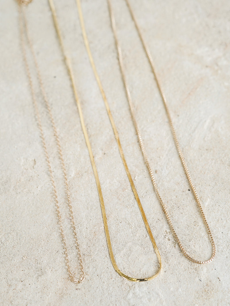 Shown: (left to right) Cable, Herringbone, Box Chains in 14k yellow gold.