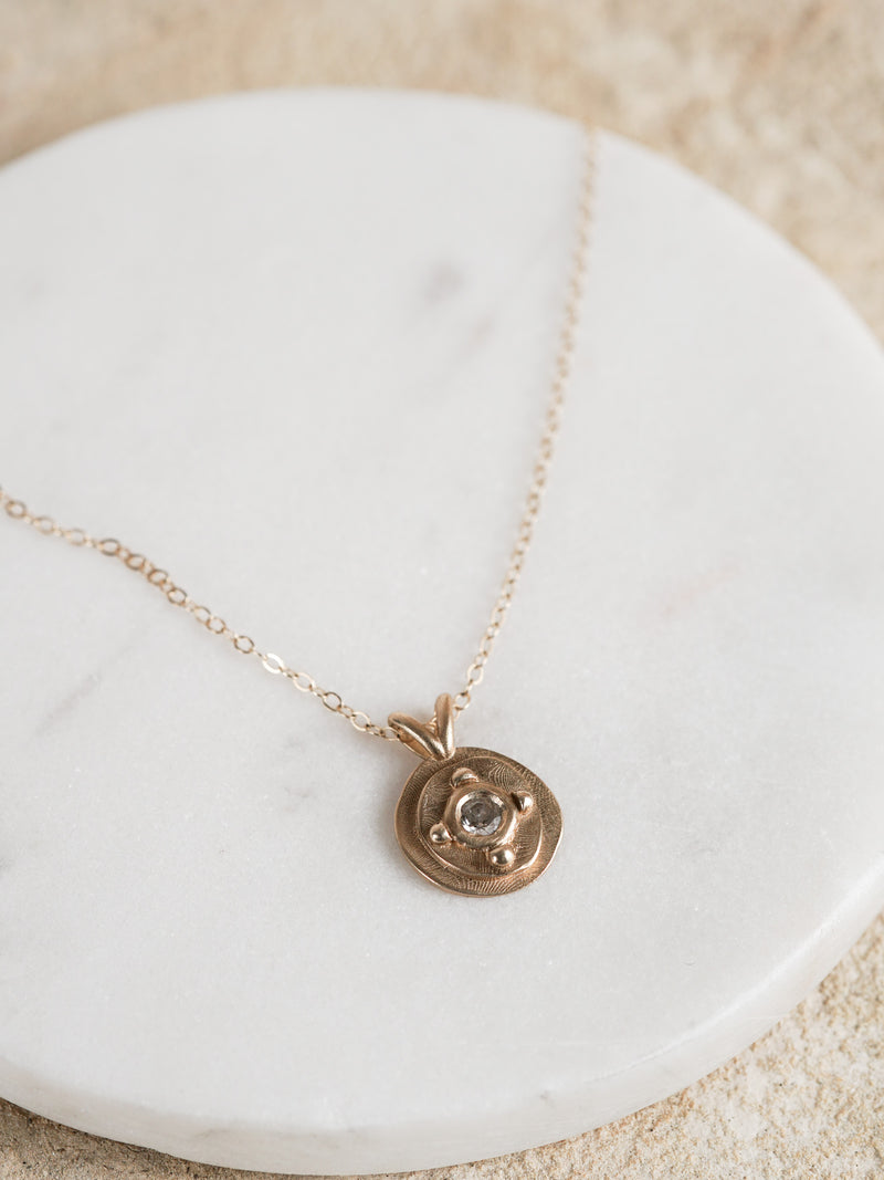 Shown: 0.25ct antique diamond in 14k yellow gold with organic texture and signature matte finish on a cable chain.