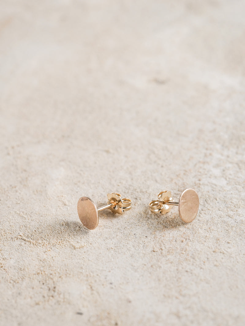 Petite disc studs in 14k yellow gold and signature matte finish.
