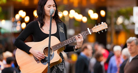 Woman busking with guitar