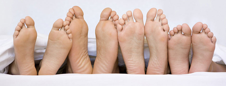 Bottom of bare feet in a row, out from under a sheet