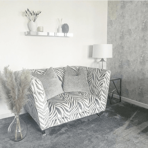 In the living room, a suite of zebra print sofas look stunning against the cool white and grey décor.