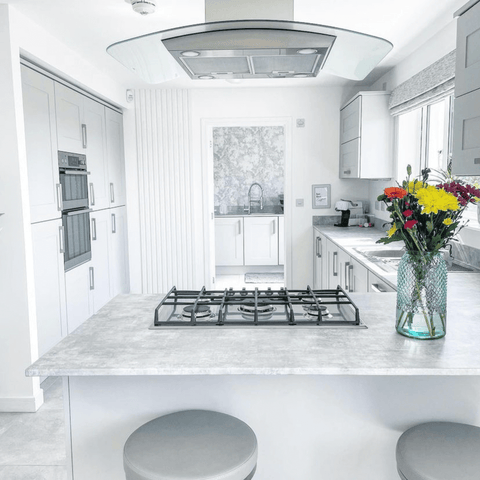 In the bright white kitchen, a vase of colourful flowers steals the show on the breakfast bar.