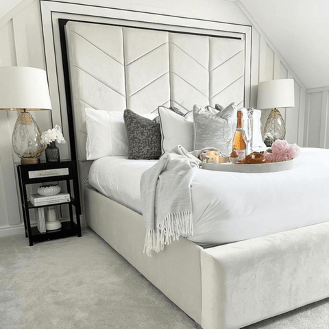 A super stylish headboard and a pair of glass lamps add glamour to the bedroom, which features Hampton and Astley Egyptian cotton sateen bedding in white.