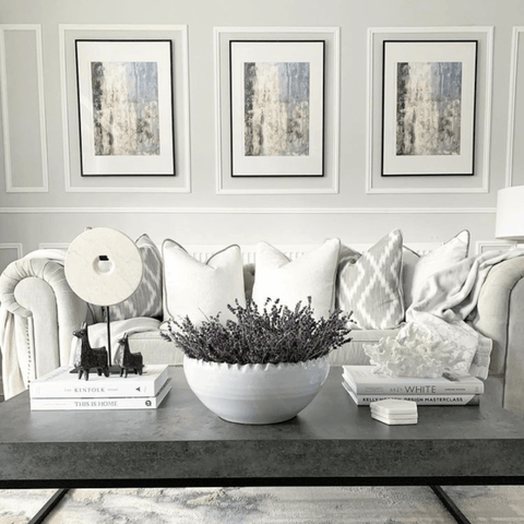 We love the use of white bordered paneling to frame the set of matching prints above the sofa