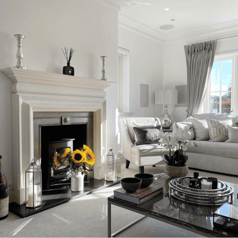 A wood burning stove adds warmth to the whites and cool neutrals of the living room, along with a cheerful vase of sunflowers.