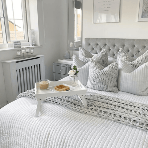 In the cool yet cosy master bedroom, sumptuous chunky knit grey fabrics are layered with Hampton and Astley long-staple cotton sateen bedding in pure white.
