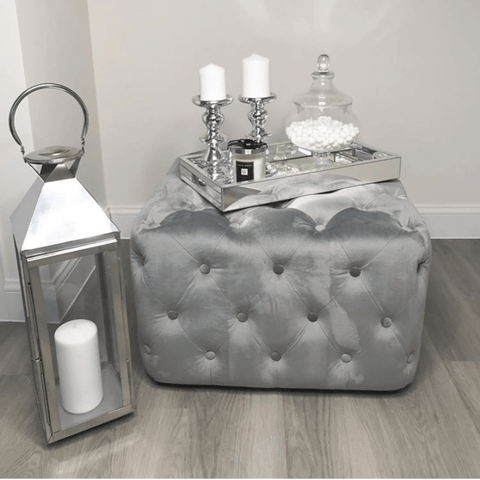 Plenty of white candles, silver accessories and an opulent velvet pouffe