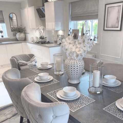 The open plan kitchen-diner features a fabulous concrete topped dining table matched with silver grey upholstered chairs