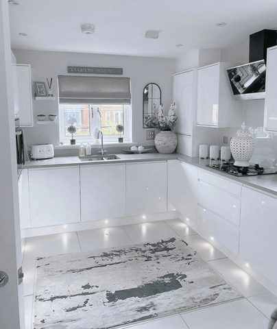 While spot lights on the kickboards and a patterned rug add character to the high-gloss white fitted kitchen.