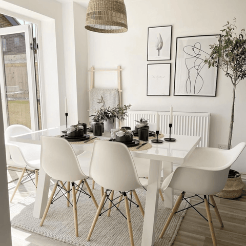Scandi styling meets the Mediterranean in the dining area, which features modern white furniture and a beautiful olive tree.