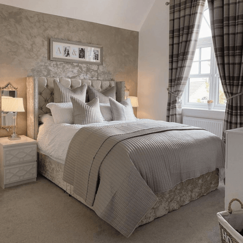 The beautiful master bedroom has sumptuous layers of bedding in stone grey and white, paired with shimmering wallpaper and upholstery