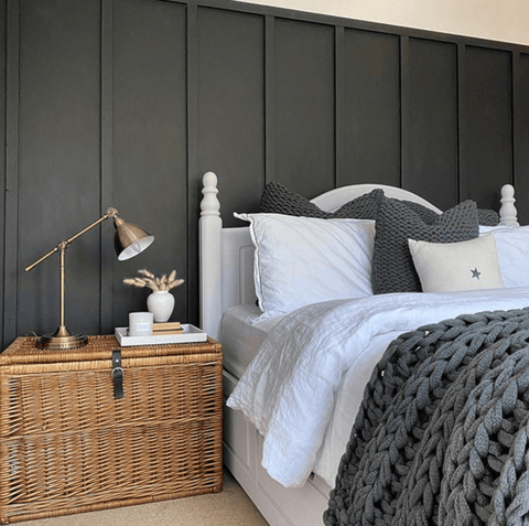 We love the dramatic dark paneling and grey chunky knit fabrics in this bedroom, along with the rather cute brass desk lamp