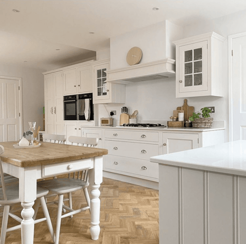In the country style kitchen, a herringbone wood floor complements the traditional oak topped table