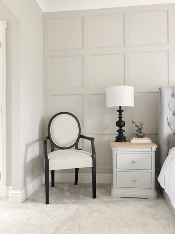 A stylish round back chair and complementary table lamp add an air of simple sophistication to the master bedroom