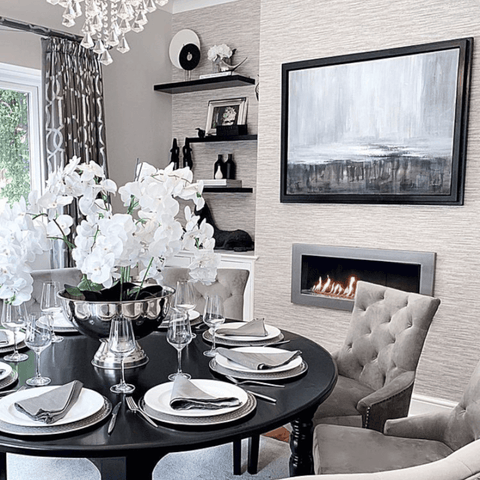 With its elegant, monochrome décor, the dining area is simply stunning. A letterbox shaped fireplace adds the perfect cosy touch