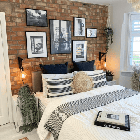 The master bedroom has a stunning exposed brickwork wall lit up by industrial wall-hanging side lamps