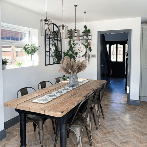 In the dining area, ironwork pendant lamps, rustic parquet flooring and a reclaimed wood table create a modern industrial feel