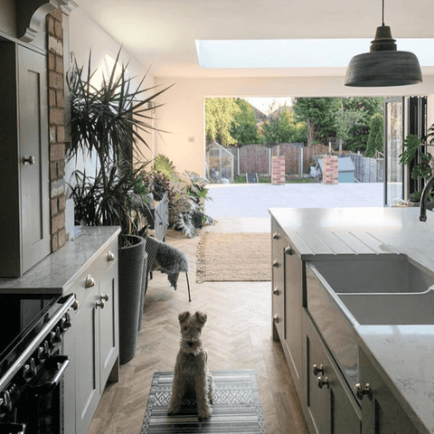 A stone grey shaker kitchen features exposed brickwork and sometimes also Shiloh the dog.