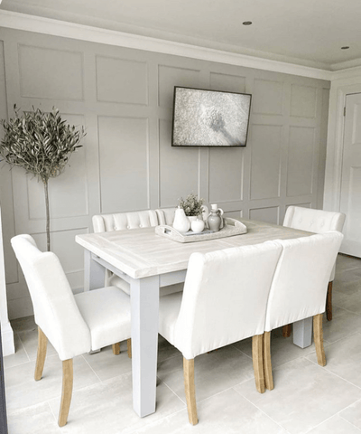 Cream linen chairs matched with an upcycled dining table create a relaxed, yet classy Mediterranean vibe in the dining area. A wall-mounted TV ensures you're always entertained while enjoying your evening tapas