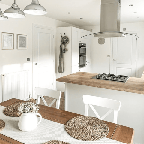 The bright white kitchen diner has oak worktops and a matching hand-crafted oak-topped table