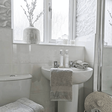 Clean white and silver tones dominate in the bathroom, which has a stack of Hampton and Astley's irresistibly soft Egyptian cotton towels in subtle grey