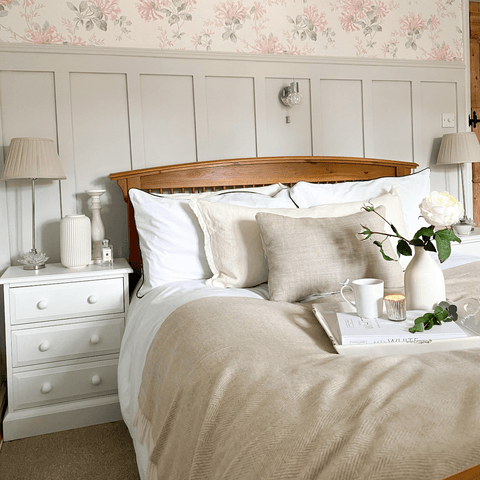 The delicate pink floral wallpaper in the bedroom is complemented by cosy white and neutral bedding.